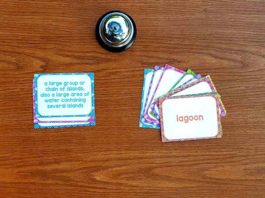 clue cards and vocabulary cards on a table with a bell