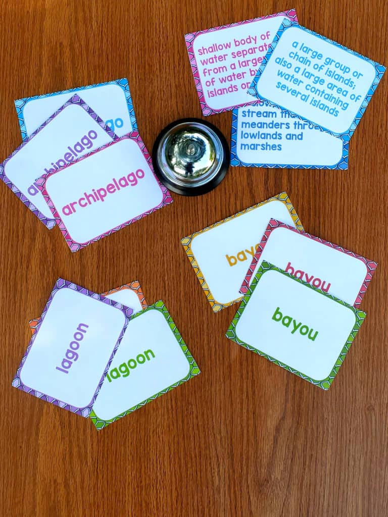 clue cards and vocabulary word cards on a table with a bell