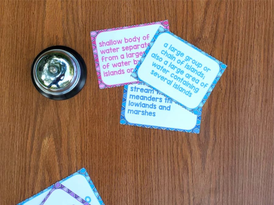 clue cards lying on a desk with a bell