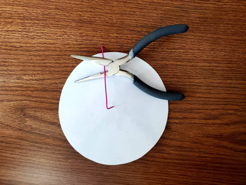 pliers cutting paper clip on back of word wheel