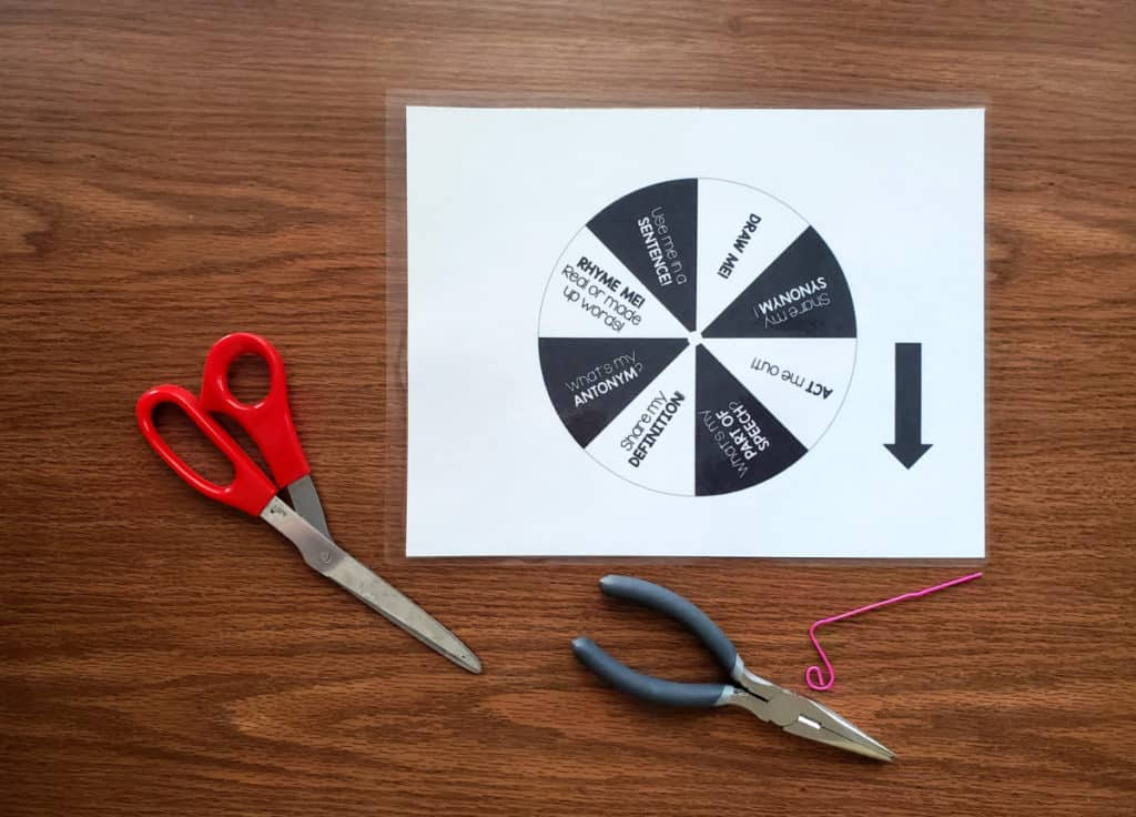 black and white word wheel on table with scissors and pliers